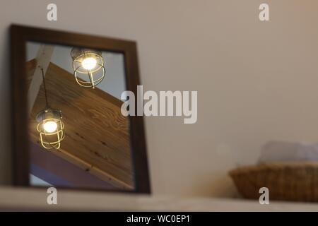 Illuminated Pendant Lights Reflecting In Mirror On Shelf - Stock Photo