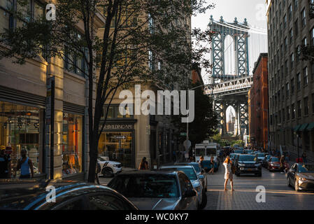 Dumbo New York, rear view of a woman taking a photo of the Manhattan Bridge in Washington Street in the Dumbo area of Brooklyn, New York City, USA. - Stock Photo