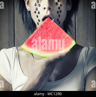 Midsection Of Mid Adult Woman Eating Watermelon Against Wooden Wall - Stock Photo