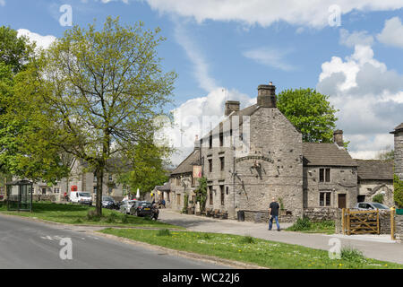 Summer street scene in the pretty Peak District village of Monyash, Derbyshire, UK; the Bull's Head pub on the right hand side. - Stock Photo