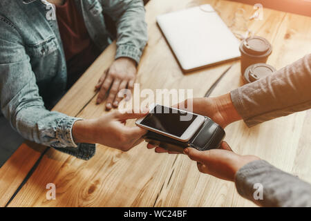 Cropped view of a person paying bill through smartphone using NFC technology in cafe. Horizontal shot - Stock Photo