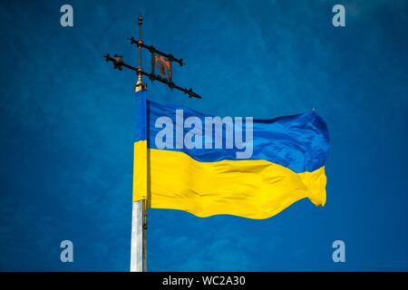 Low Angle View Of Flag Waving Against Blue Sky - Stock Photo