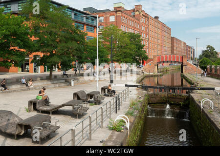 People enjoy the sunshine by the Rochdale Canal in Ancoats, Manchester, UK. - Stock Photo
