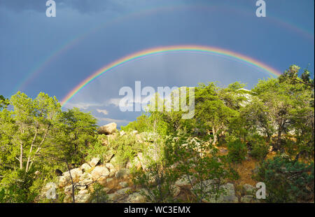 A Double rainbow shines brightly over the high desert landscape. - Stock Photo