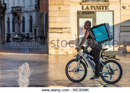 Deliveroo delivery rider in Dijon in the Côte-d'Or Department, Bourgogne-Franche-Comté region of France. - Stock Photo