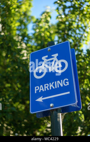Low Angle View Of Bicycle Parking Sign Against Trees - Stock Photo