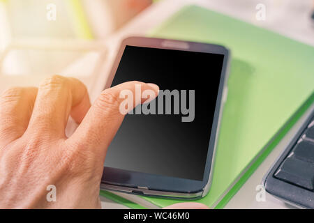 Close-up Of Hand Touching Mobile Phone At Desk - Stock Photo