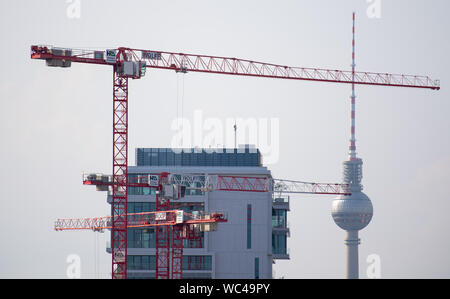 Berlin, Germany. 27th Aug, 2019. High construction cranes are standing next to a new building on a construction site at the East Side Gallery. In the background, the Berlin television tower rises into the sky. Credit: Monika Skolimowska/dpa-Zentralbild/dpa/Alamy Live News - Stock Photo