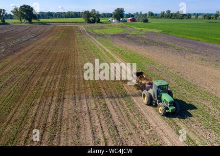 Three Oaks, Michigan - Dairy farmer Howard Payne spreads manure on a field as fertilizer. - Stock Photo