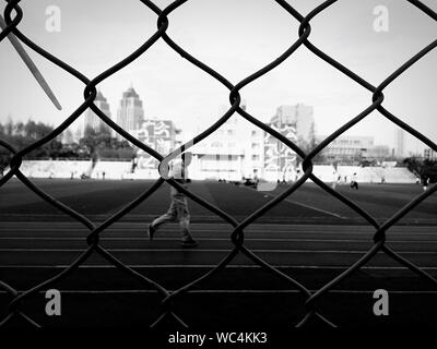 Man Running On Track Behind Wire Fence - Stock Photo