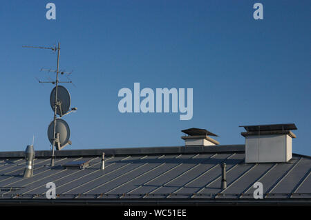 Antenna And Satellite Dish On House Roof Against Clear Blue Sky - Stock Photo