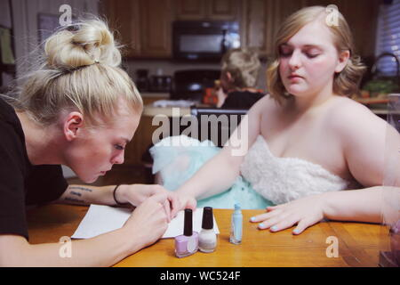 Woman Applying Nail Polish On Teenage Girl Hand At Home - Stock Photo