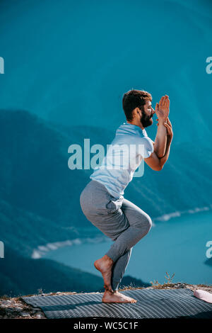 Fitness, sport, and lifestyle concept - Healthy man making yoga exercises on mountain - Stock Photo