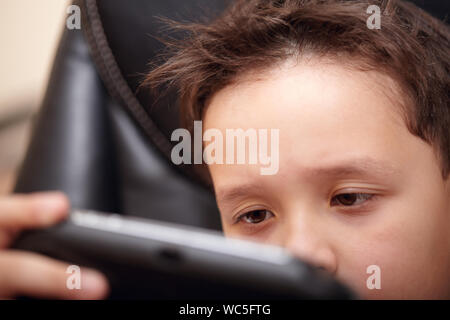Boy tired of playing his portable game console. - Stock Photo