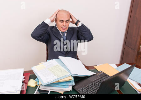 Frustrated Businessman Looking At Documents On Desk In Office