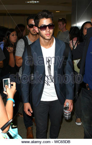 Los Angeles, CA - The Jonas Brothers arrive at LAX airport after a short trip. Joe, along with girlfriend Blanda Eggenschwiler, Nick and Kevin were greeted by a large crowd of fans asking for autographs and pictures before leaving. AKM-GSI, August 16, 2013 - Stock Photo