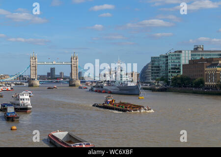A large barge in the Pool of London on the River Thames with a view of the iconic Tower Bridge and HMS Belfast, viewed from London Bridge - Stock Photo