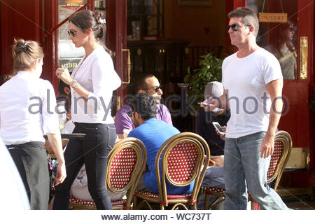 London, UK - Simon Cowell and Lauren Silverman enjoy a romantic lunch al fresco in London, enjoying the beautiful afternoon. The expecting couple chatted and held each other's hands at the table, showing a lot of affection for one another. Over the weekend, the X-Factor producer and his pregnant lover enjoyed some quality time together in Saint-Tropez, cuddling and kissing out in the open. Simon seems to be lovestruck by his new love, despite the recent divorce announcement between Lauren and Simon's friend Andrew Silverman. AKM-GSI, August 28, 2013 - Stock Photo