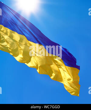 textile flag of Ukraine develops against a clear blue sky,  state symbol of an independent state on a summer sunny day - Stock Photo