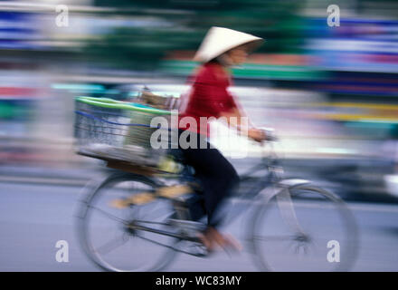 Side View Of Street Vendor Riding Bicycle On Road - Stock Photo