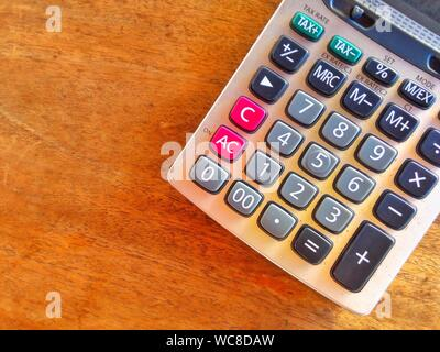 Directly Above Shot Of Calculator On Wooden Table - Stock Photo