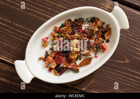 Lot of pieces of lavender strawberry ice tea in ceramic stewpan flatlay on brown wood - Stock Photo
