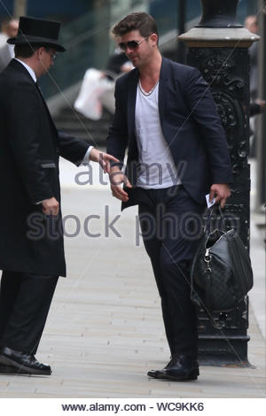 London, UK - Robin Thicke is greeted by a concierge as he arrives at his hotel in London. The 'Blurred Lines' singer looked stylish in a pinstriped blue suit with sunglasses and carried a designer Louis Vuitton Damier Graphite luggage bag. AKM-GSI, September 25, 2013 - Stock Photo