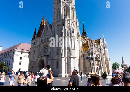 Budapest, Hungary - August 10, 2019: Tourists visit the St. Matthias Church. - Stock Photo