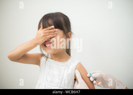 Cropped Hand Of Doctor Holding Girl With Syringe Against White Background - Stock Photo