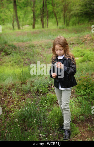 Stylishly dressed blonde little girl schoolgirl is trying to save a white dandelion. She stands in a green glade. Walk in the park. - Stock Photo