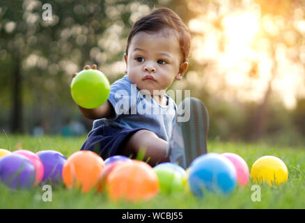 Cute Baby Boy Playing With Colorful Balls On Grassy Field At Park - Stock Photo