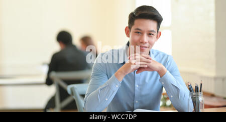 Young businessman smiling confidently at the camera while sitting in modern office room - Stock Photo