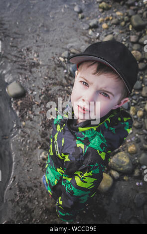 High Angle Portrait Of Boy Standing At Beach - Stock Photo