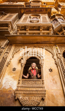 A Caucasian tourist posing for a picture in one of the many amazing Havelis in Jaisalmer, Rajasthan, India. - Stock Photo