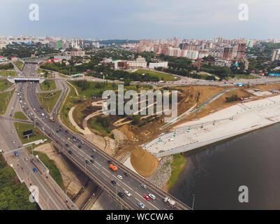 White River in the city center on the background of private houses with colorful roofs on a slope with green trees and modern high-rise buildings. Bel - Stock Photo
