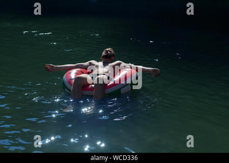An inflatable circle floats on the river, in which a young bearded man of caucasian nationality sleeps. ecotourism in a mountain river ecosystem, outd - Stock Photo