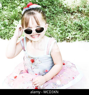 Portrait Of Cute Smiling Girl Wearing Sunglasses While Sitting On Rug At Field - Stock Photo
