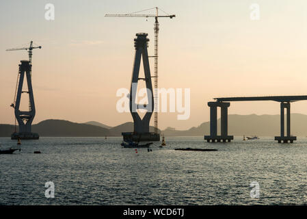 Incomplete Bridge Columns By Cranes Amidst Sea Against Sky During Sunset - Stock Photo
