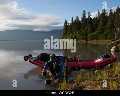 Man Filling Water In Container While Crouching By Boat At Lakeshore Against Trees - Stock Photo