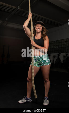 An attractive young woman with long hair and short pants is posing at the rope.The smiling athlete is doing a functional fitness workout in a gym. - Stock Photo