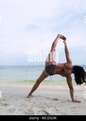Rear View Of Woman In Bikini Stretching At Beach - Stock Photo