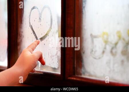 Close-up Of Woman Drawig Heart On Window - Stock Photo