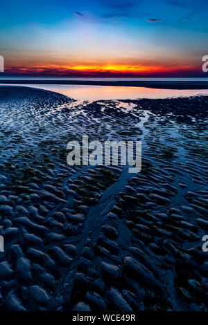 Colourful sky over the north sea after sunset at the beach on Juist, East Frisian Islands, Germany. - Stock Photo