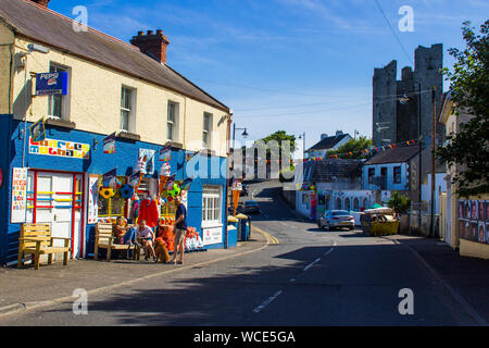 8 August 2019 Tourists sit outside a colourful village shop trading in small gifts, ice cream and confectionary on the main street of Ardglass, County - Stock Photo