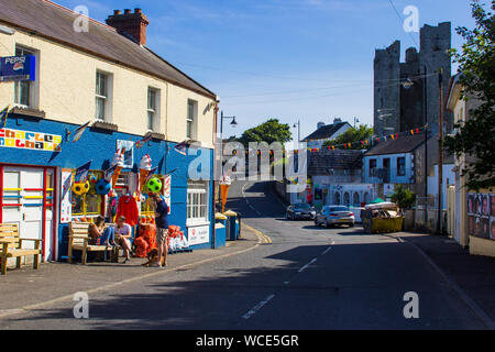 8 August 2019 Customers relaxing outside a colourful village shop trading in small gifts, ice cream and confectionary on the main street in Ardglass, - Stock Photo