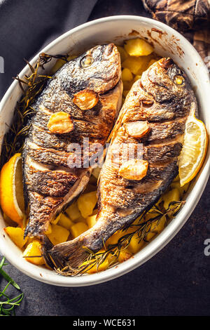 Roasted mediterranean fish bream with potatoes rosemary and lemon - Stock Photo