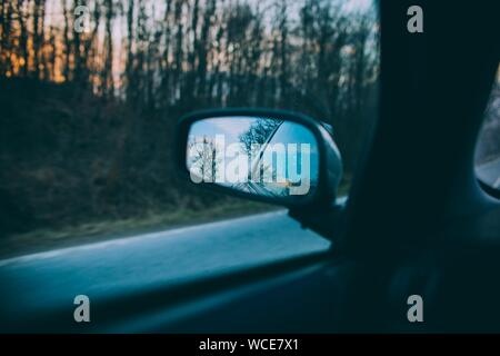A beautiful shot of trees and the blue sky reflected on a cars side mirror with a blurred road in the background - Stock Photo