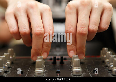 Close up wide angle shot of female dj hands adjusting frequency knobs on sound mixer panel.Professional audio equipment for hip hop disc jockey.Musici - Stock Photo