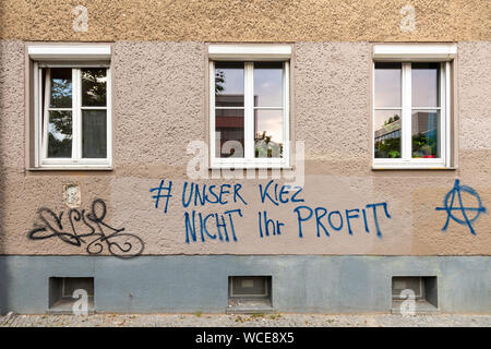 Protest slogan on an old residential building against real-estate investors in Berlin Prenzlauer Berg, Germany.