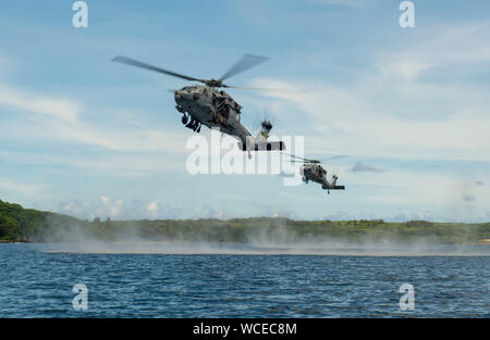"""190827-N-QL471-1011  SANTA RITA, Guam (Aug. 27, 2019) MH-60S Seahawk helicopters, attached to the """"Island Knights"""" of Helicopter Sea Combat Squadron (HSC) 25, carry U.S. Marines, assigned to 3rd Reconnaissance Battalion, 3rd Marine Division and 3rd Marine Division, Explosive Ordnance Disposal 1st Platoon, and members of Her Majesty's New Zealand Ship Matataua (HMNZS Matataua) during a helocasting subject matter expert knowledge exchange as part of Exercise HYDRACRAB. HYDRACRAB is a quadrilateral exercise conducted by forces from Australia, Canada, New Zealand, and U.S. Naval forces. The purpos - Stock Photo"""